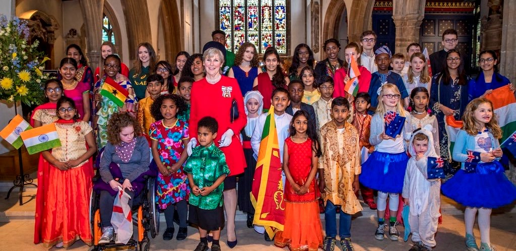 Many children and young adults of many nationalities in national costumes posing with the Lord Lieutenant inside Chelmsford Cathedral
