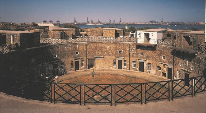A view of Harwich Redoubt from the top gallery, showing the circular central yard surrounded by doors. Above many of the doors is a porthole window and beside the doors are portrait-format rectangular paned windows. The uniformity of the building suggests a military use. Iron-looking fencing surrounds the inside of rooftop gallery, breached by at least three rooftop perches, presumably for bringing items up from the central yard. In the distance port cranes are visible on the far side of the water.