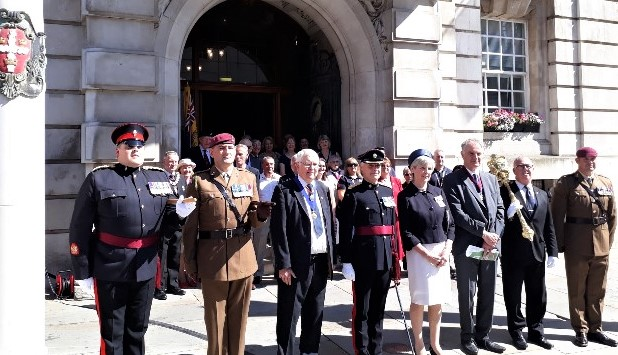 A row of officials including soldiers in parade dress and men in suits with chains of office stand with the Lord-Lieutenant in the centre. They are outside the front entrance to Colchester Town hall and there is a small crowd of people behind them, also dressed smartly. The entrance is a high arched doorway to an impressive building with the town's coat of arms to the left of the image.