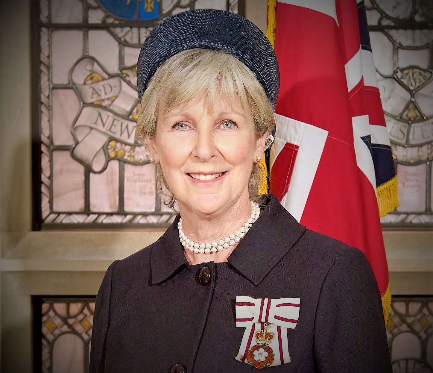 A head and shoulders shot of Lord Lieutenant of Essex Jennifer Tolhurst. She wears a dark jacket with the Lord Lieutenant medal on her left breast. She wears a necklaces of two short strings of pearls, pearl stud earrings and a dark pillbox hat. Behind her is a Union Jack unfurled and stained glass windows.