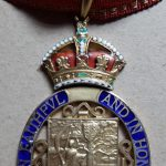 Close up image of an oval badge topped with a crown, attached to a red riband with gold-edging. The oval surround is blue with the words 'In Action Faithful In Honour Clear' and surrounds a silver rectangular engraving of a person on horseback next to a tree containing a shield with a crest.